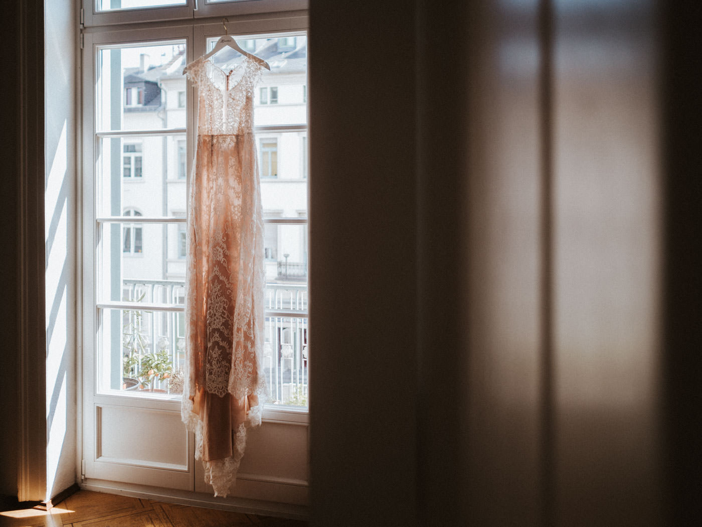 Boho Vintage Wedding Dress hanging at a window