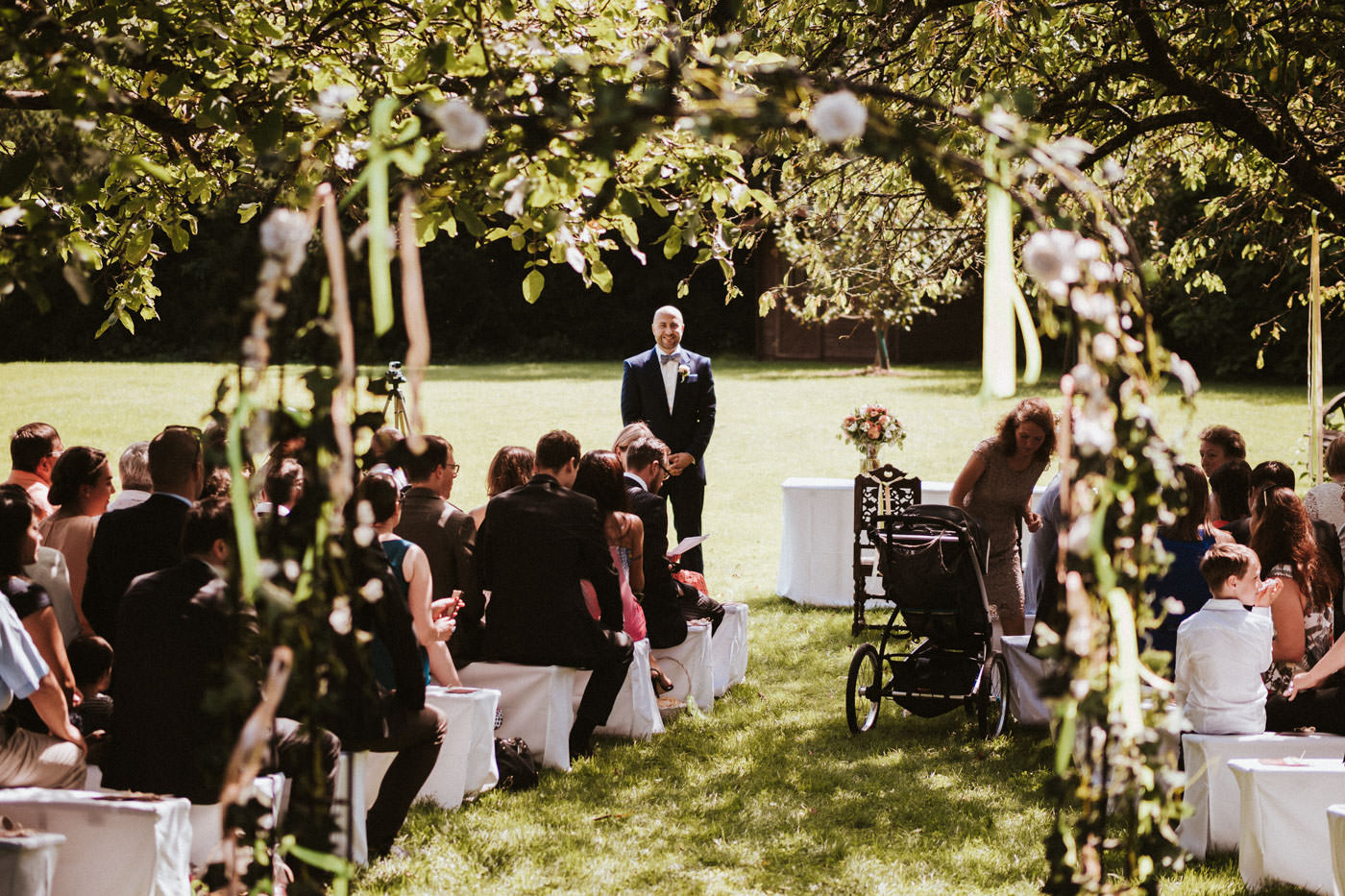 Groom and wedding guests at the outdoor ceremony under a tree