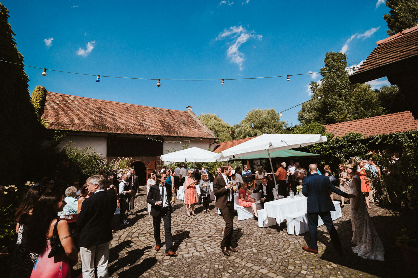Relaxed atmosphere during a wedding reception in the courtyard of Weidenmühle winery