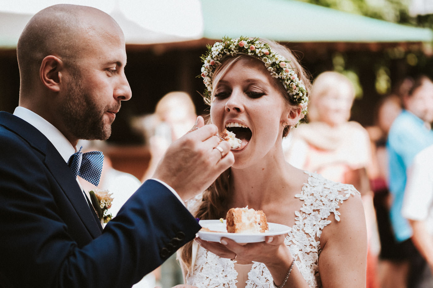 Groom feeds bride with wedding cake