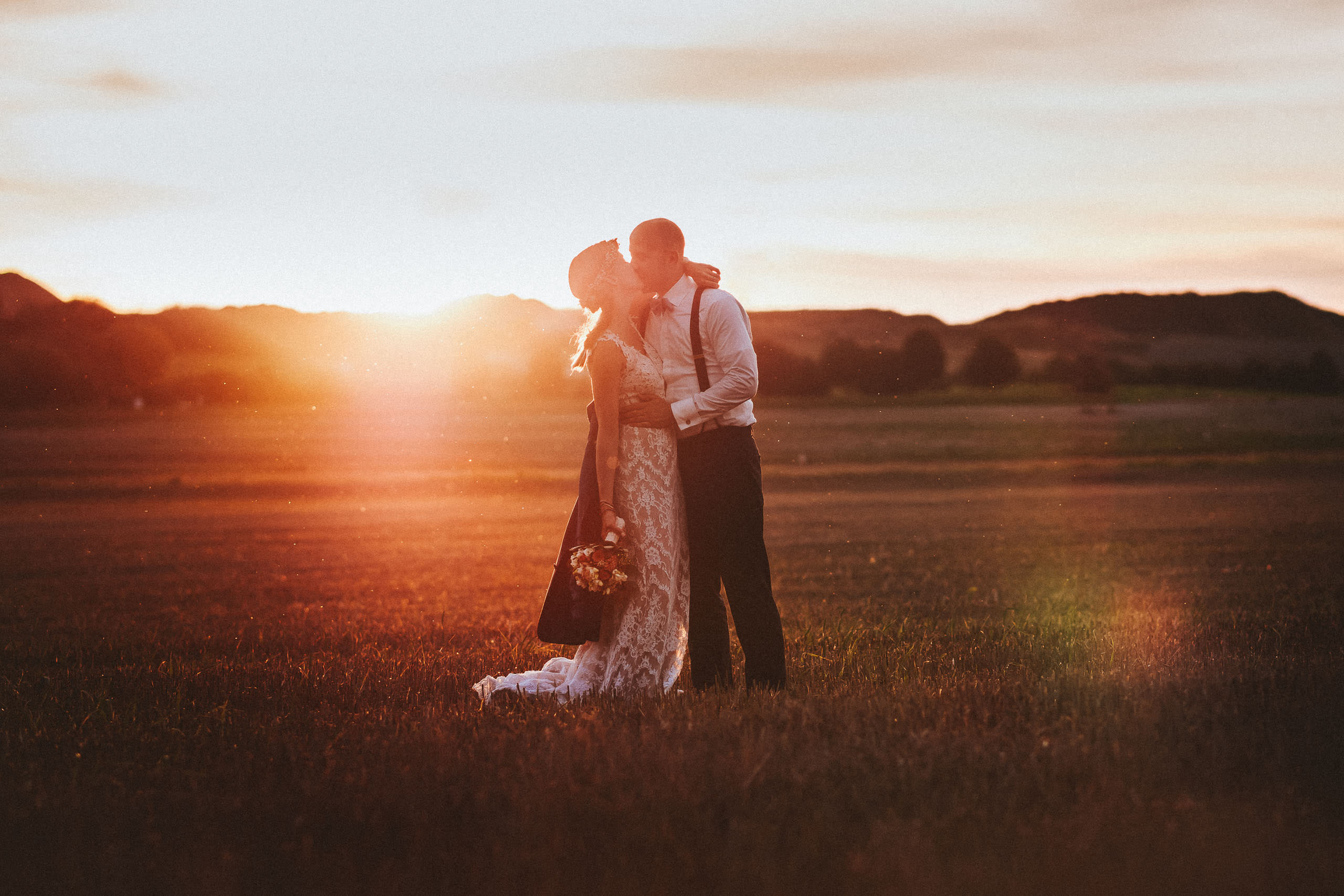 Weddingphoto at dawn, couple kissing with sunset