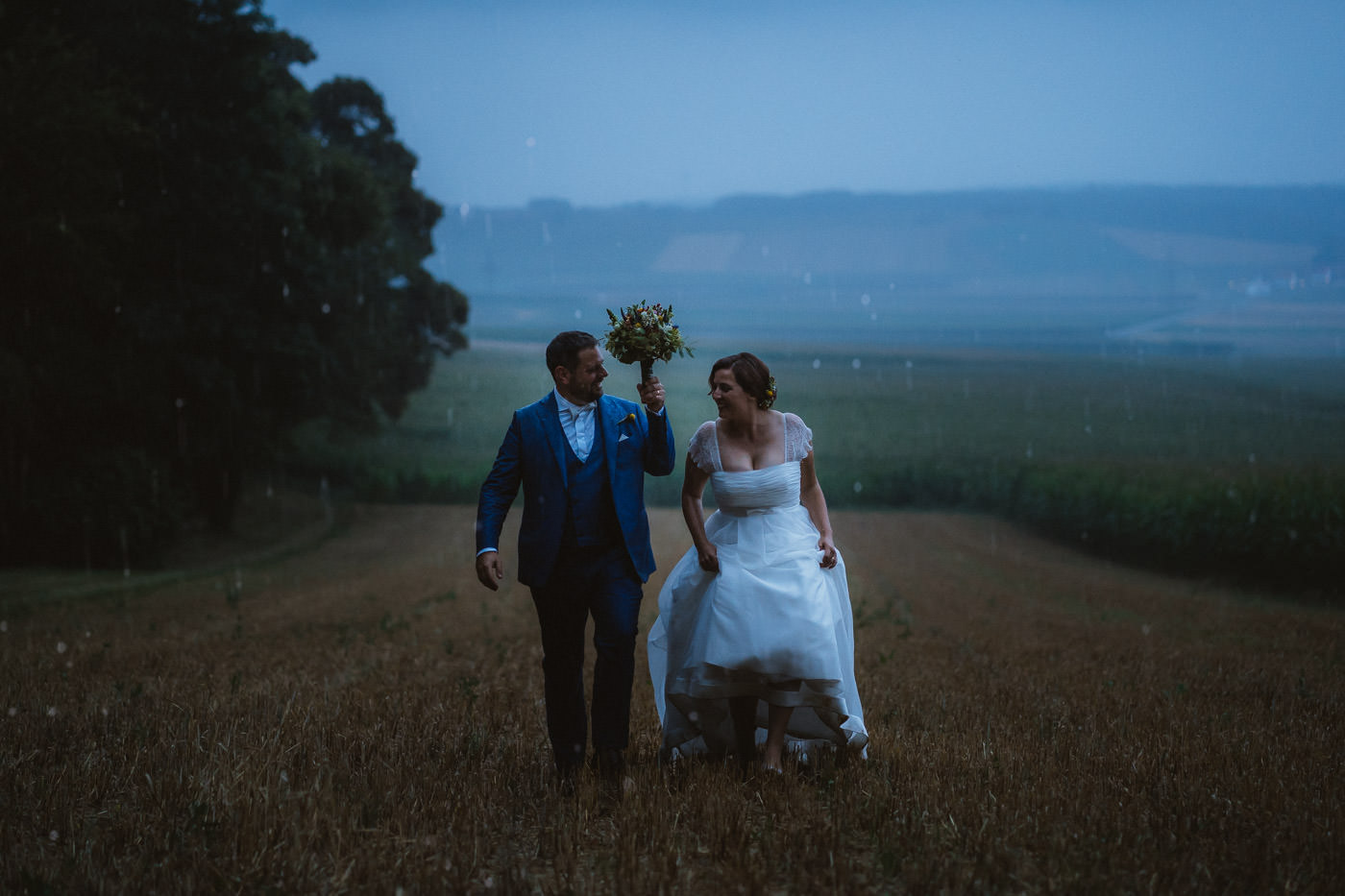 bridal couple in the pouring rain - rainy day wedding photos