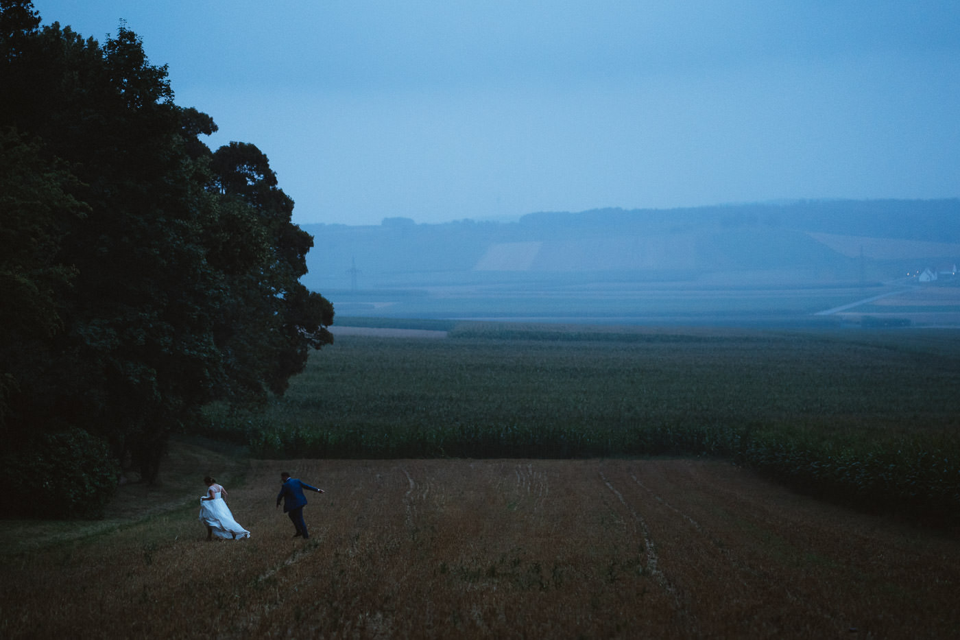 bridal couple in the rain with a lot of landscape